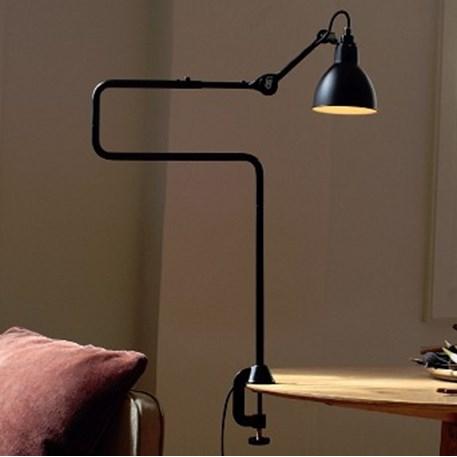 Sfeerfoto van de volledig zwarte klemlamp die een bijzettafel verlicht